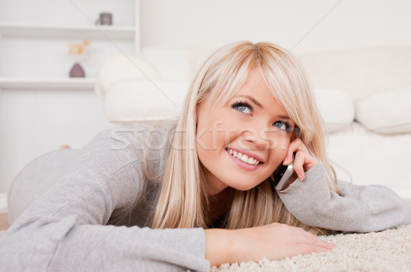 Beautiful happy blond woman talking on cell phone lying down on a carpet in the living room Stock photo © wavebreak_media