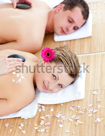 dark-haired woman lying on her belly with a flower on her ear surrounded by flowers Stock photo © wavebreak_media