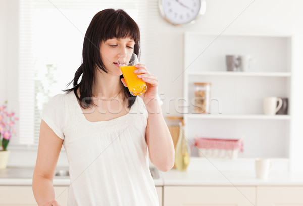 Lovely brunette drinking a glass of orange juice while standing in the kitchen Stock photo © wavebreak_media