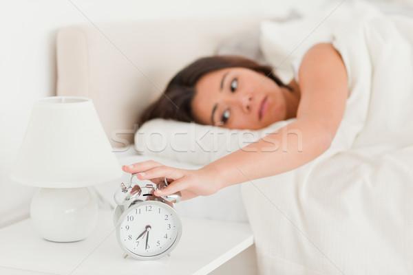 cute woman waking under sheet turning off alarm clock in bedroom Stock photo © wavebreak_media