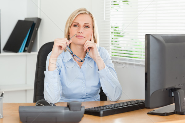 Thoughtful woman with glasses looking into camera in an office Stock photo © wavebreak_media
