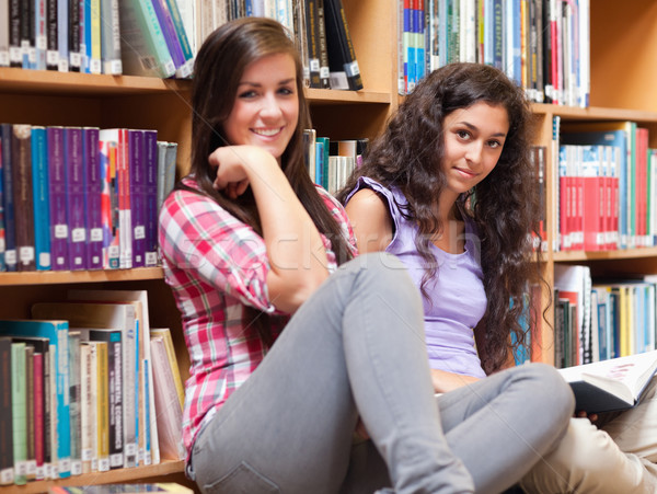 Female students holding a book in a library Stock photo © wavebreak_media
