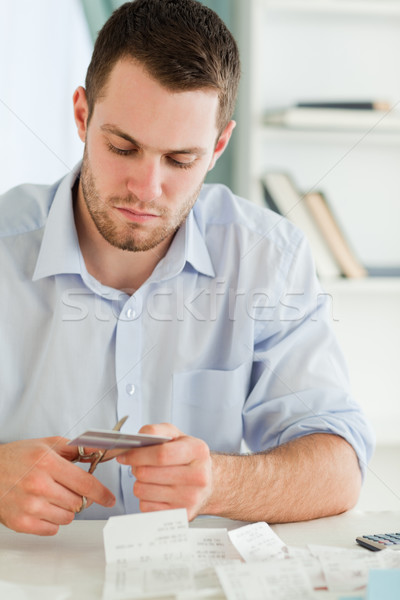 Stock photo: Young businessman cutting his credit card