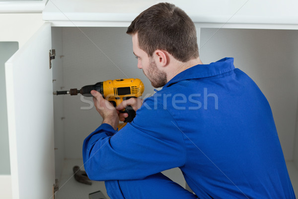 Handyman fixing a door in a kitchen Stock photo © wavebreak_media