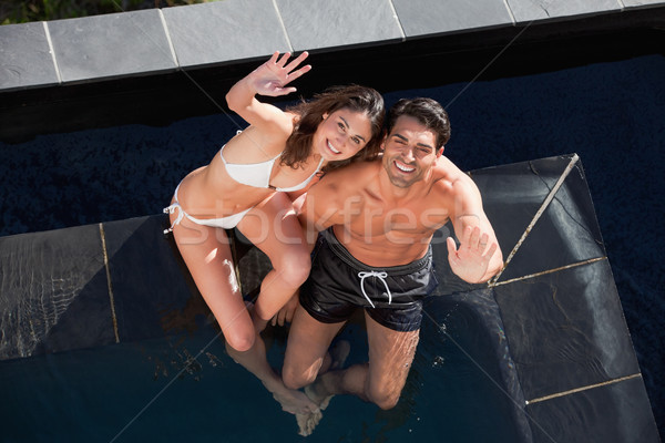 Above view of a smiling couple waving at the camera in a swimming pool Stock photo © wavebreak_media