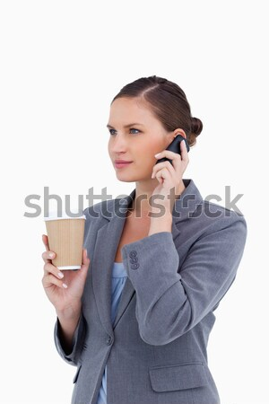 Tradeswoman with paper cup on her cellphone against a white background Stock photo © wavebreak_media