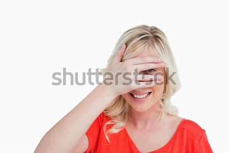 Attractive blonde woman trying to see through her fingers placed in front of her face Stock photo © wavebreak_media