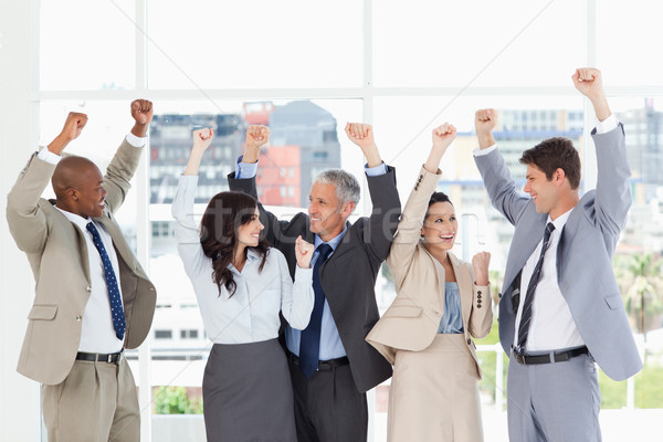 Smiling business people looking at each other and raising their arms in success Stock photo © wavebreak_media