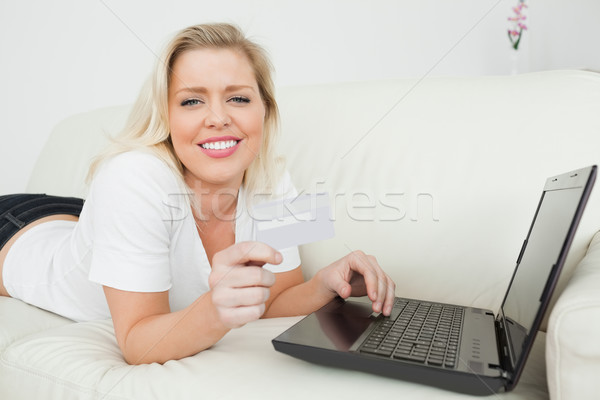 Casual woman lying on a white sofa with a credit card and a laptop Stock photo © wavebreak_media