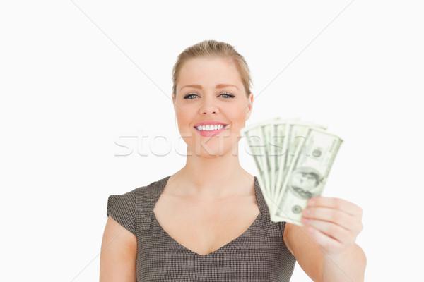 Smiling woman showing dollars banknotes against white background Stock photo © wavebreak_media