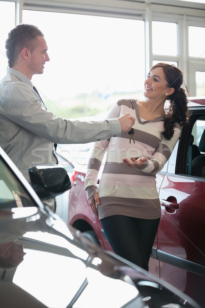 Stock photo: Smiling woman receiving keys from a salesman in a car shop