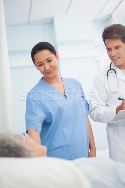 Doctor and nurse looking at a patient in hospital ward Stock photo © wavebreak_media