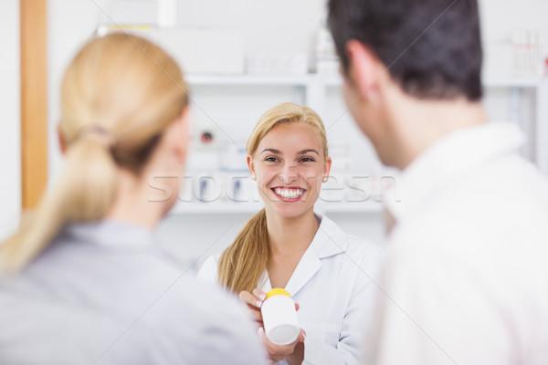 Szőke nő gyógyszerész tart drog doboz gyógyszertár Stock fotó © wavebreak_media