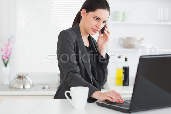 Foto stock: Mulher · chamada · usando · laptop · cozinha · computador · telefone