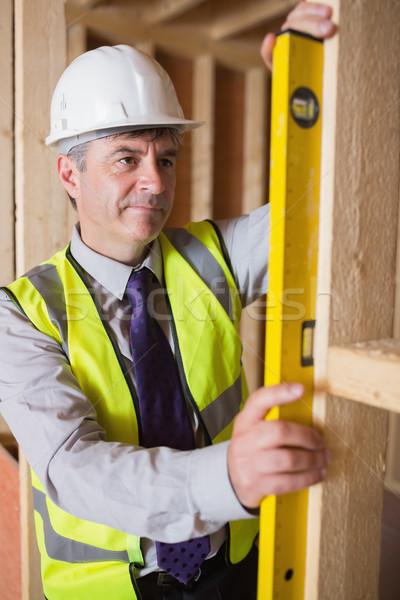 Man with warning vest and helmet measuring wooden frame with spirit level Stock photo © wavebreak_media
