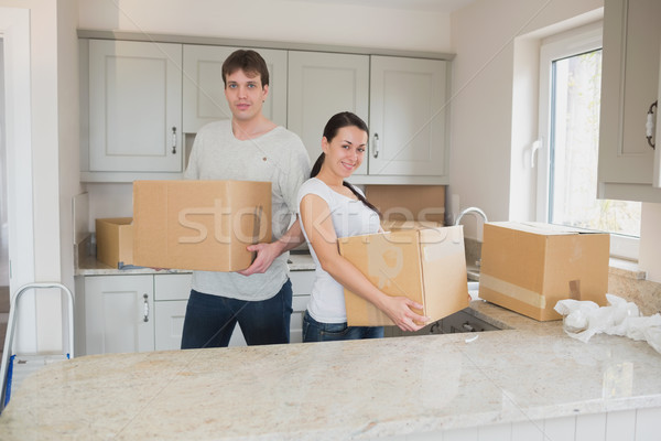 Two young people standing in the kitchen and holding boxes for a relocation Stock photo © wavebreak_media