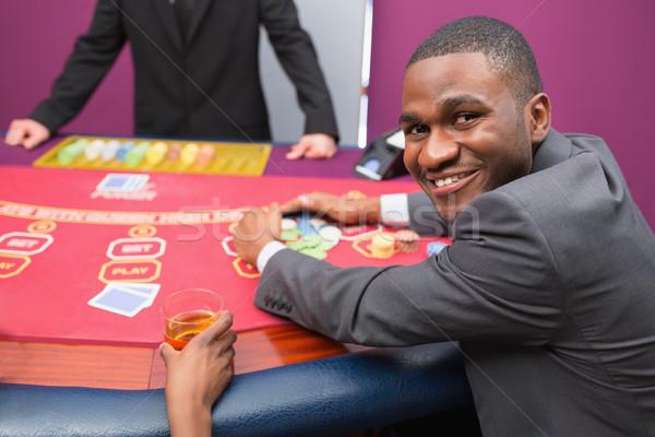 Happy man taking his winnings in poker game in casino Stock photo © wavebreak_media