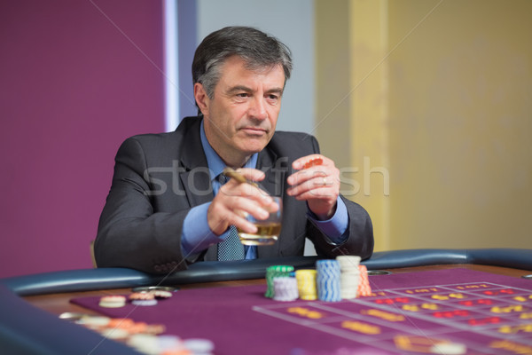 Man looking at the roulette table looking angry while holding a glass Stock photo © wavebreak_media