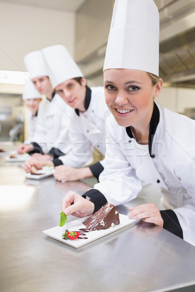 Chef's team garnishing slices of cake and smiling in the kitchen Stock photo © wavebreak_media