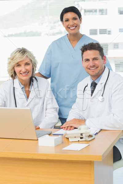 Smiling doctors with laptop at medical office Stock photo © wavebreak_media