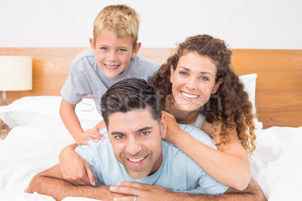 Cute jonge familie glimlachend camera bed Stockfoto © wavebreak_media