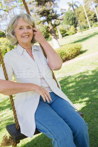 Lächelnd reife Frau Sitzung Swing Park Porträt Stock foto © wavebreak_media