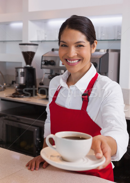 Pretty young barista offering cup of coffee smiling at camera Stock photo © wavebreak_media