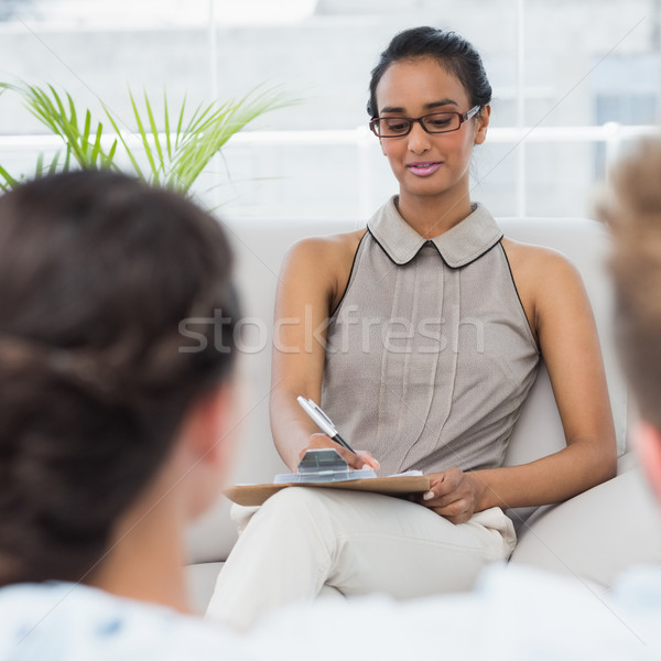 Therapist talking with couple on the couch and taking notes Stock photo © wavebreak_media