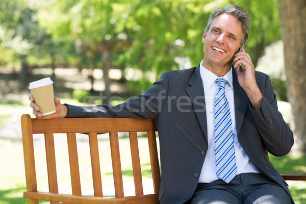 Businessman with disposable cup answering cellphone  Stock photo © wavebreak_media