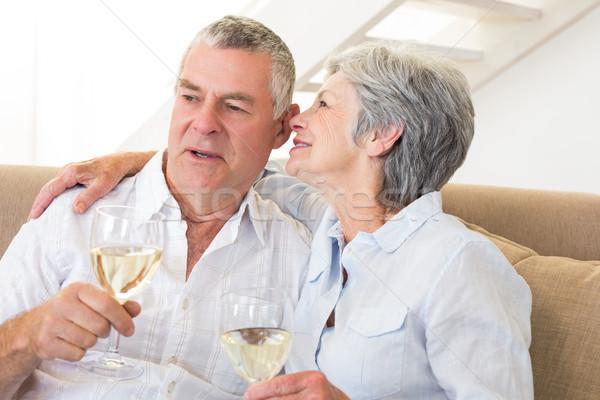 Stock photo: Senior couple sitting on couch drinking white wine