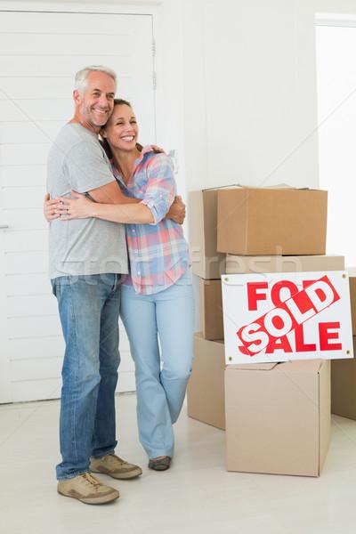 Happy couple standing and hugging beside sold sign Stock photo © wavebreak_media