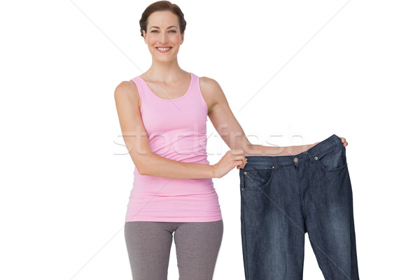 Portrait of a beautiful fit woman holding an old jeans Stock photo © wavebreak_media