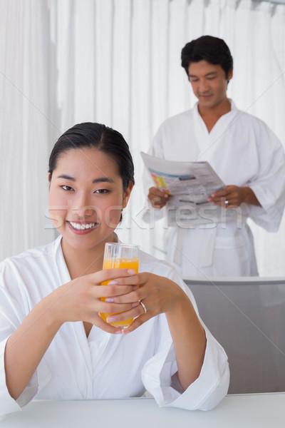 Mulher roupão de banho suco de laranja namorado casa sala de estar Foto stock © wavebreak_media