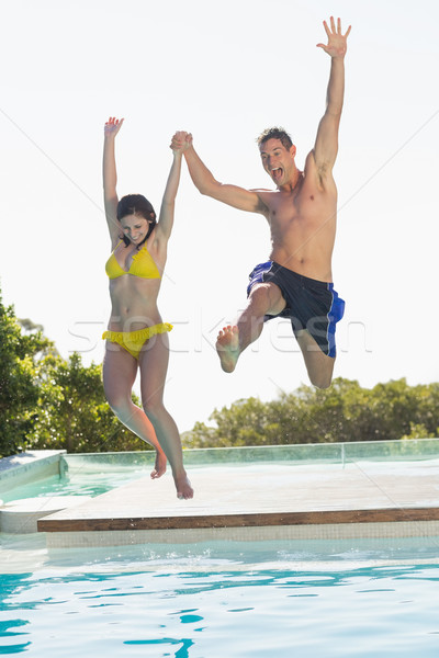 Excited couple jumping into swimming pool on holidays Stock photo © wavebreak_media