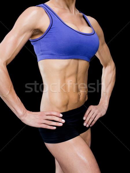Female bodybuilder posing with hands on hips mid section Stock photo © wavebreak_media