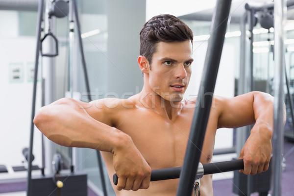 Shirtless muscular man using biceps pull up in gym Stock photo © wavebreak_media