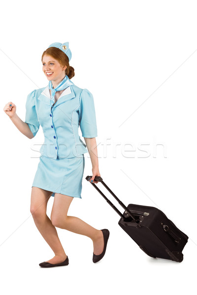 Pretty air hostess pulling suitcase Stock photo © wavebreak_media