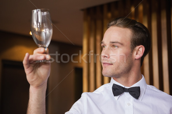 Handsome waiter inspecting a wine glass Stock photo © wavebreak_media