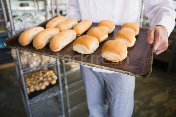 Mid section of a baker holding tray with bread Stock photo © wavebreak_media