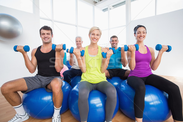 People sitting on balls and lifting weights in fitness club Stock photo © wavebreak_media