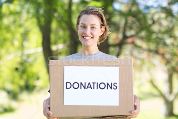 Happy volunteer in the park holding box Stock photo © wavebreak_media