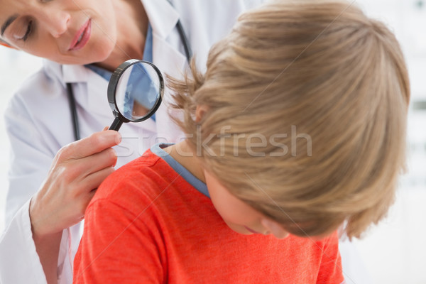 Doctor examining patient with magnifying glass  Stock photo © wavebreak_media
