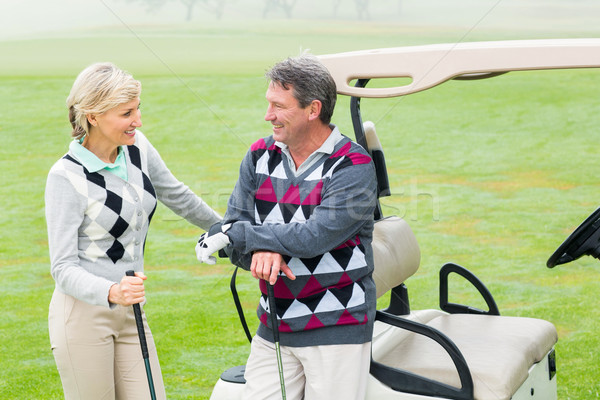 Happy golfing couple with golf buggy behind  Stock photo © wavebreak_media