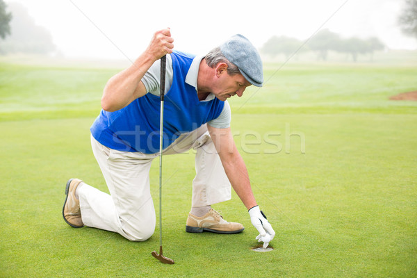 Happy golfer kneeling on the putting green Stock photo © wavebreak_media