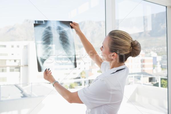 Doctor looking at Xray beside windows  Stock photo © wavebreak_media
