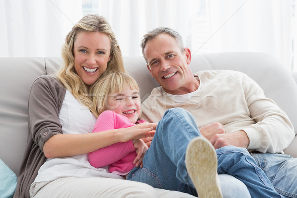 Stock photo: Happy parent tickling their cute daughter on the couch