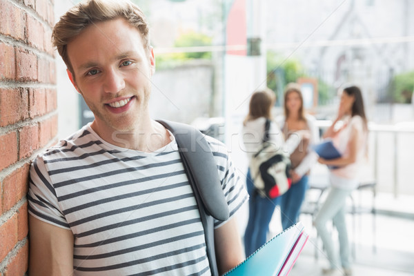 Handsome student smiling and holding notepads Stock photo © wavebreak_media