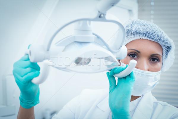 Female dentist in surgical mask adjusting light Stock photo © wavebreak_media