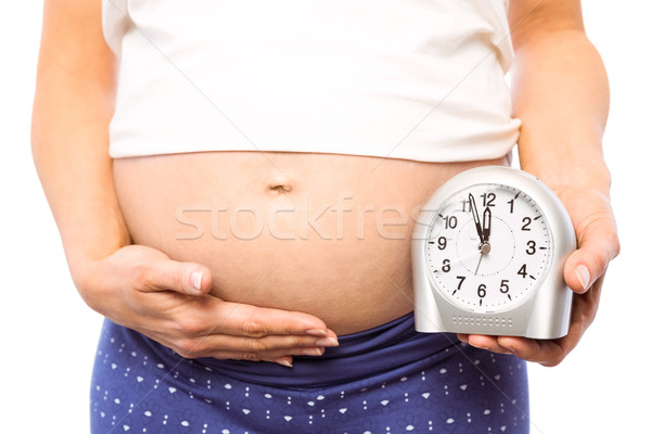 Pregnant woman showing clock and bump Stock photo © wavebreak_media