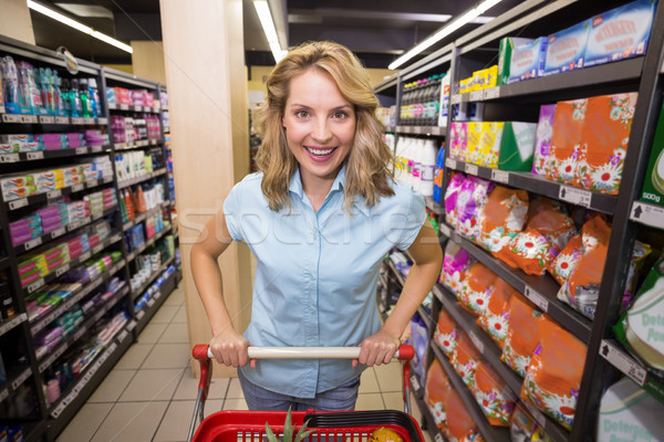 Portrait of a smiling blonde woman in aisle with her trolley  Stock photo © wavebreak_media